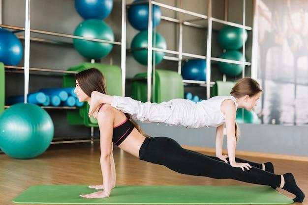 Hija y madre haciendo ejercicio juntos en el gimnasio Foto gratis