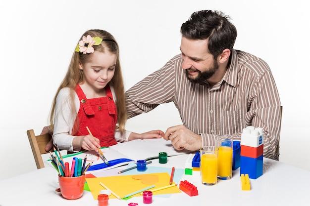 La hija y el padre dibujando y escribiendo juntos sobre fondo blanco. Foto gratis