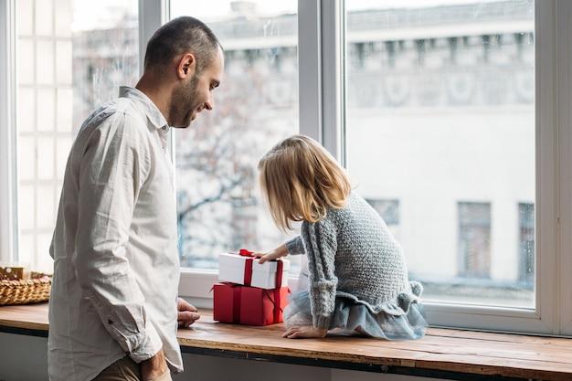 Hija y padre jugando con cajas de regalo junto a la ventana Foto Premium