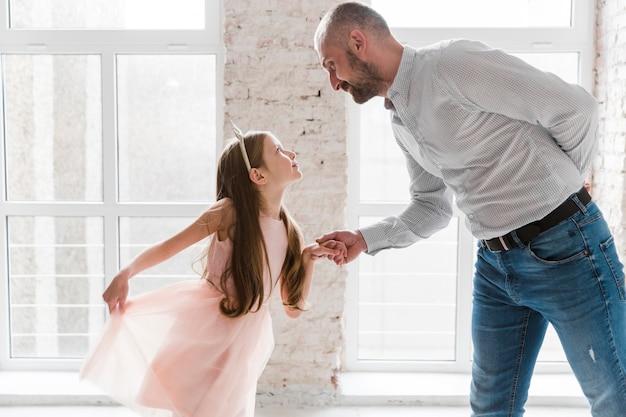 Hija y papá bailando el día del padre Foto gratis