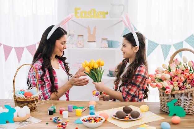 Hija que da tulipanes de flores amarillas a su madre con la preparación del día de pascua en casa Foto gratis