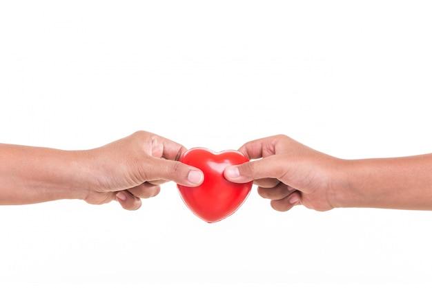 Hija sosteniendo y dando corazón rojo a la mano de su madre aislada en blanco Foto Premium
