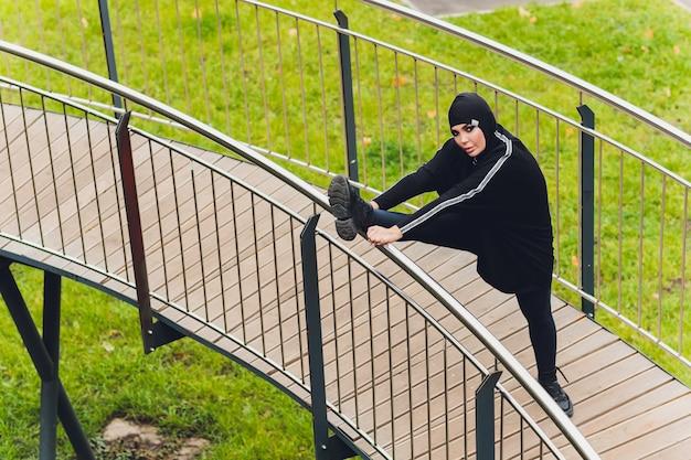 Hijab mujer haciendo ejercicio en el puente de la pasarela temprano en la mañana Foto Premium