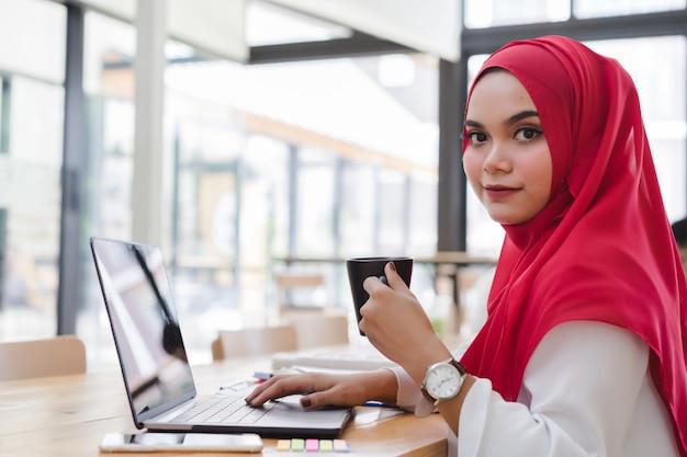 Hijab rojo del contador musulmán asiático atractivo que trabaja con la computadora portátil y que sostiene una taza de café en el trabajo compartido o la cafetería. gente de negocios que trabaja en concepto de trabajo conjunto. Foto Premium
