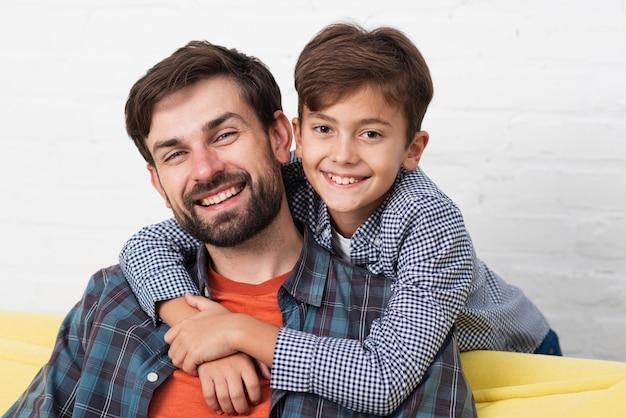 Hijo abrazando a su padre sonriente Foto gratis