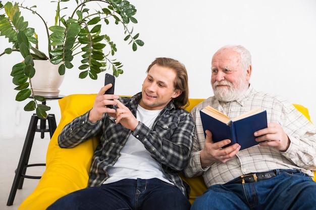 Hijo mostrando información del padre en el teléfono. Foto gratis
