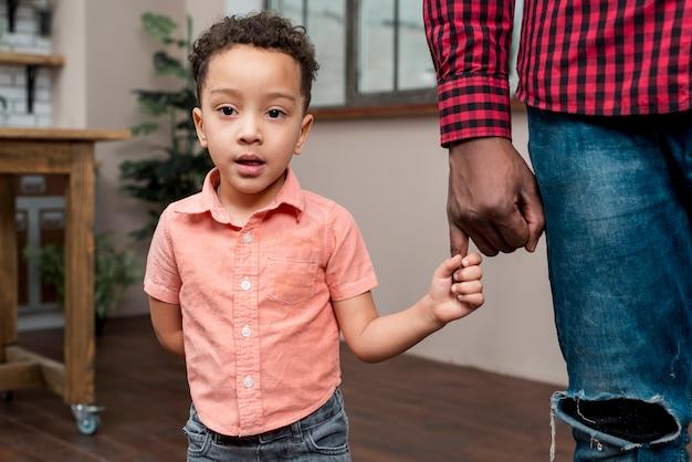 Hijo negro sosteniendo la mano de los padres Foto gratis
