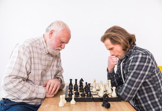 Hijo y padre jugando al ajedrez Foto gratis