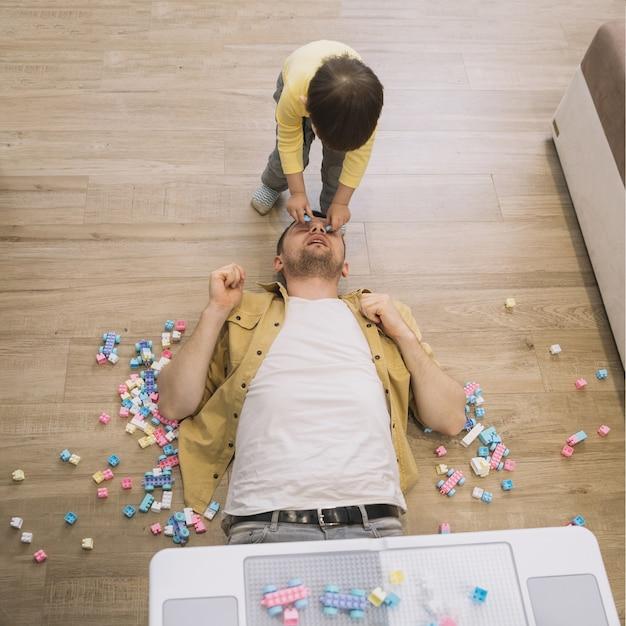 Hijo poniendo piezas de lego de la cara del padre Foto gratis