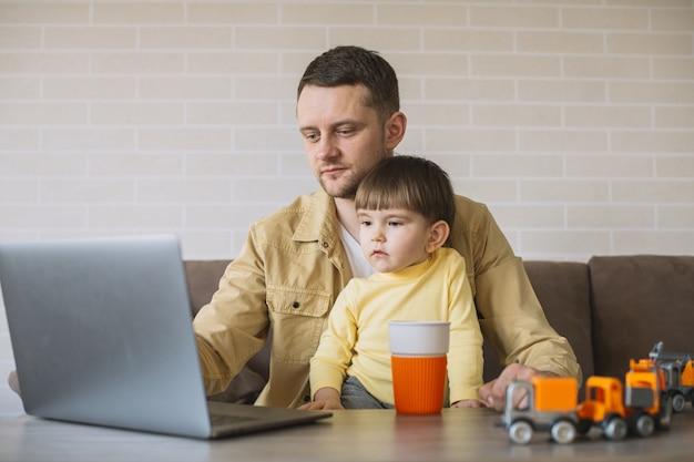 Hijo quedándose con el padre mientras trabaja desde casa Foto gratis