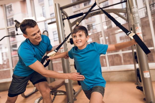 Hijo realiza un ejercicio y papá le dice a su hijo. Foto Premium