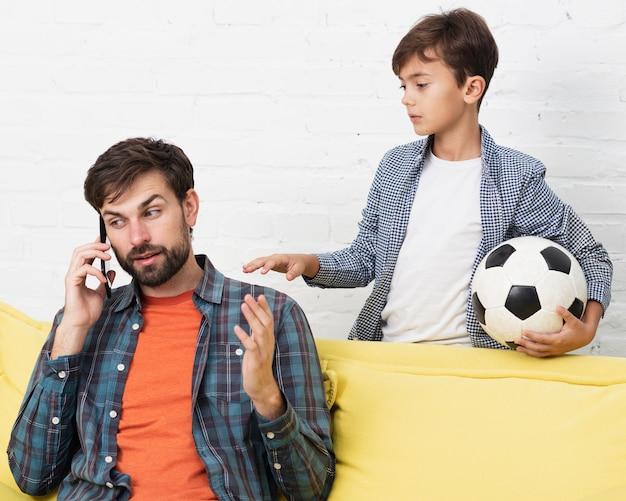 Hijo sosteniendo una pelota y padre hablando por teléfono Foto gratis