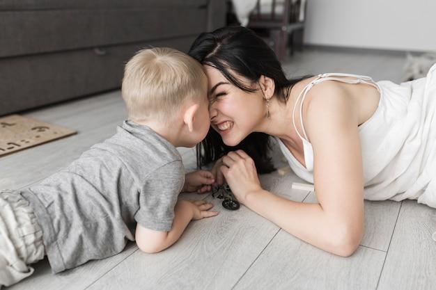 Hijo y su madre acostados en el piso de madera frotándose la nariz Foto gratis