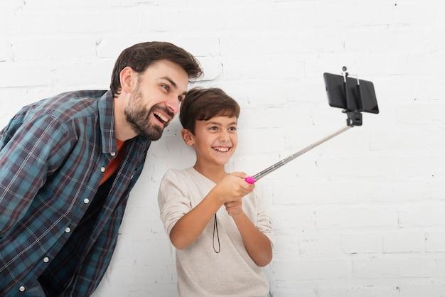 Hijo tomando una selfie con su padre Foto gratis