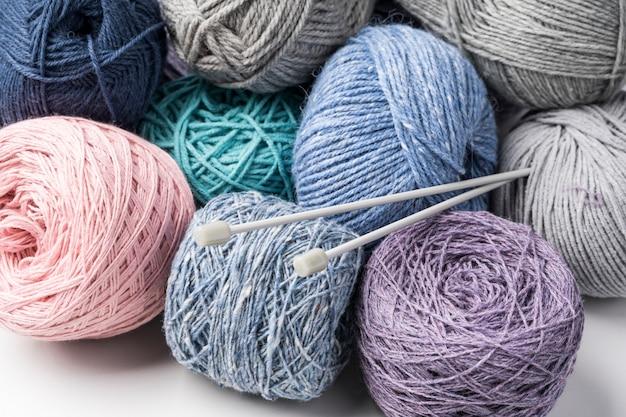 Hilados de lana de colores con agujas de plástico. Foto gratis