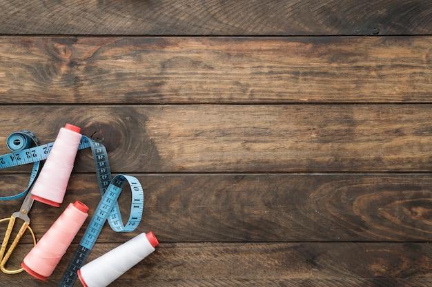 Hilos cerca de tijeras y cinta métrica Foto gratis