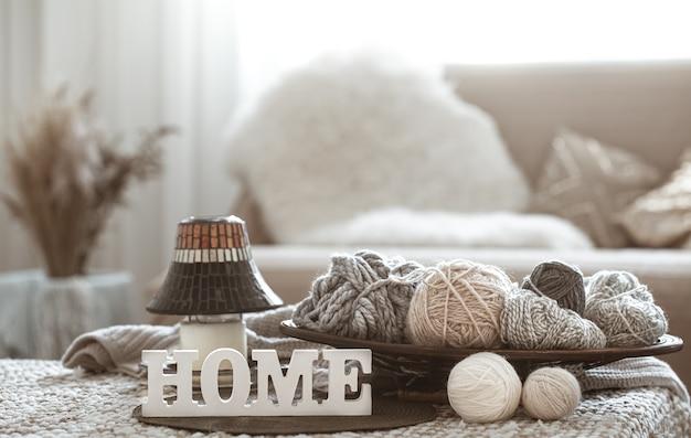 Hilos de tejer en la mesa y letras de madera caseras Foto gratis