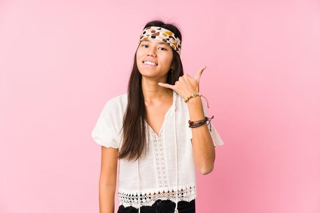 Hippie chino joven aislado mostrando un gesto de llamada de teléfono móvil con los dedos. Foto Premium