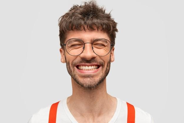 Hipster hombre barbudo positivo sonríe ampliamente, tiene expresión complacida, se ríe de algo gracioso, cierra los ojos, Foto gratis