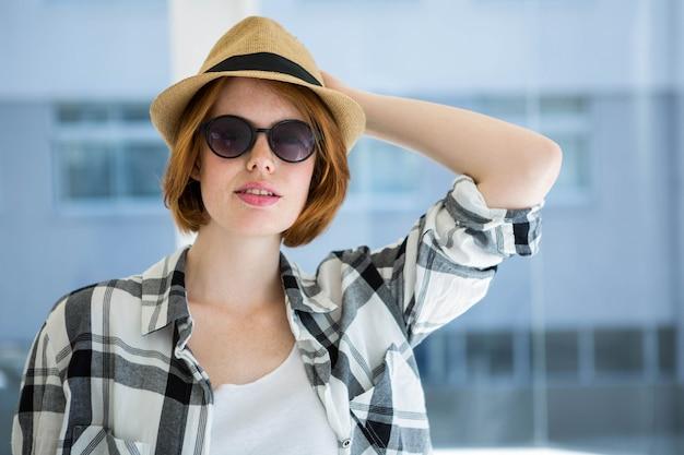 Hipster de moda con gafas de sol delante de una ventana Foto Premium