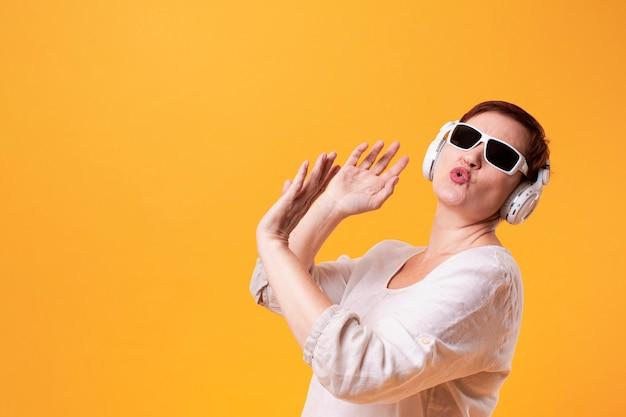 Hipster senior mujer bailando y escuchando música Foto gratis