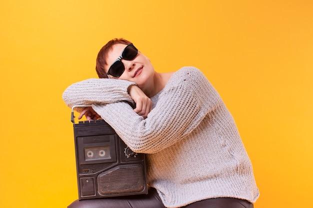 Hipster senior mujer descansando sobre un reproductor de cassette vintage Foto gratis