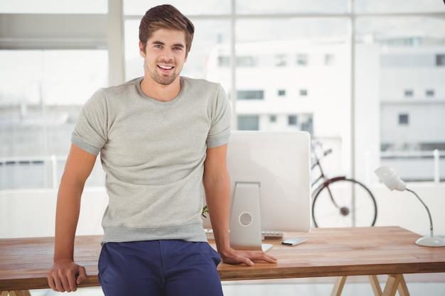 Hipster sonriendo mientras se inclina en el escritorio en la oficina Foto Premium