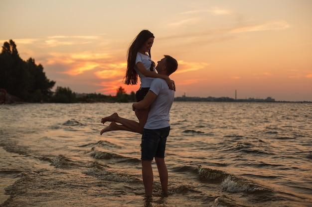 Historia de amor en la playa joven hermosa pareja amorosa abrazando en la playa al atardecer. Foto Premium