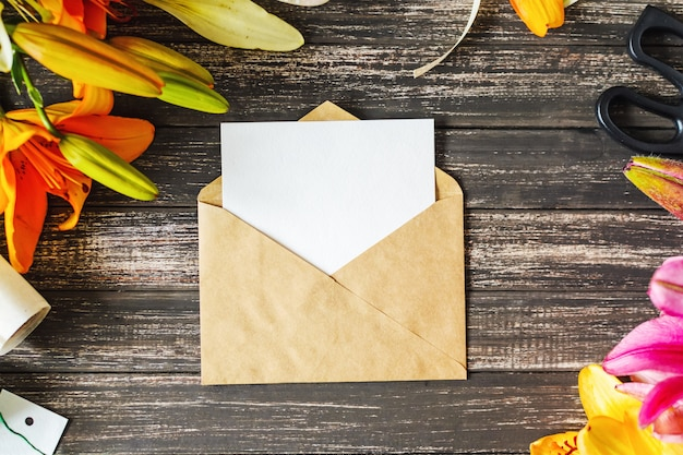 Hoja en blanco blanca en sobre del arte y decoraciones con las flores en la tabla de madera. diseño de tarjeta de felicitación. burlarse de la vista superior Foto Premium