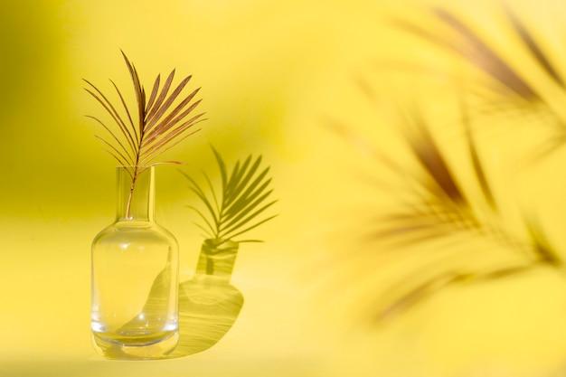 Hoja de palma dorada en florero de vidrio. Foto Premium