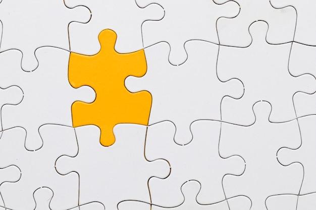 Hoja de rompecabezas blanco con pieza de rompecabezas amarillo en el centro Foto gratis