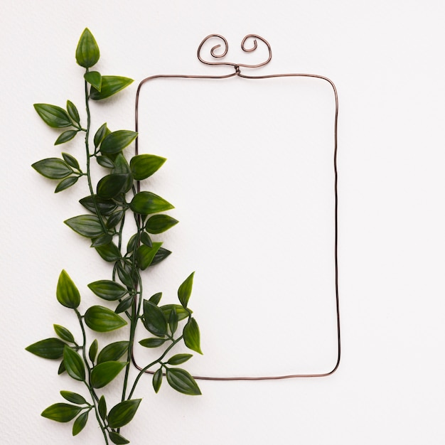 Hojas artificiales verdes cerca del marco rectangular en la pared blanca Foto gratis