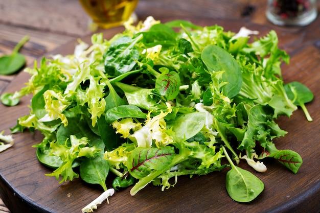 Hojas frescas de la ensalada de la mezcla en un fondo de madera. Foto gratis