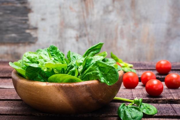 Hojas frescas de espinaca baby en un tazón y tomates cherry en una mesa de madera Foto Premium