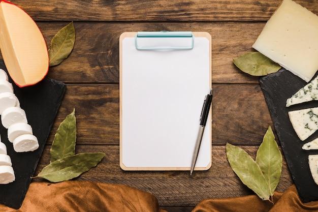 Hojas de laurel; queso; paño; bolígrafo y portapapeles en escritorio de madera Foto gratis