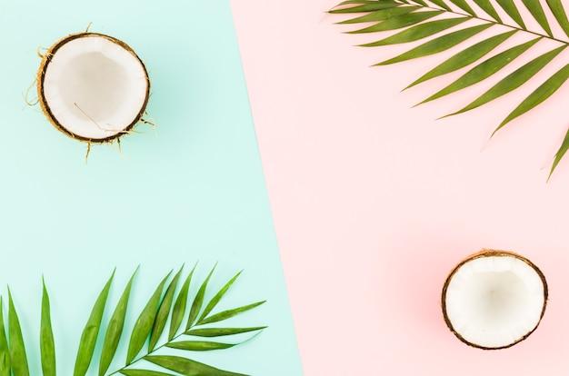 Hojas de palma verde con cocos en mesa brillante Foto Premium