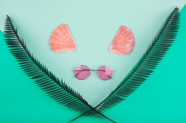Hojas de palmera cruzadas decorativas; vieira y gafas de sol sobre fondo de menta Foto gratis