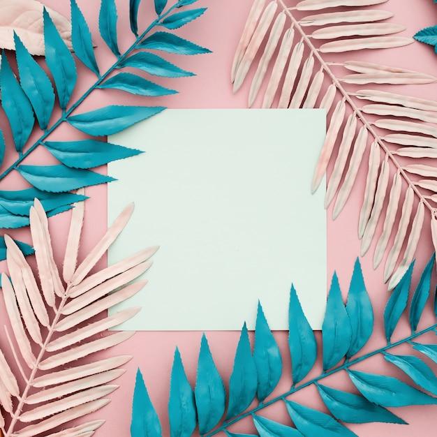 Hojas de palmeras tropicales con papel blanco en blanco sobre fondo rosa Foto gratis