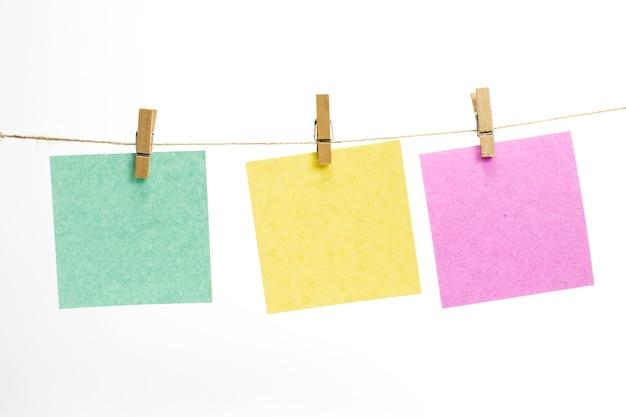 Hojas de papel de color vacías para notas, marcos que cuelgan de una cuerda con pinzas para la ropa y aislados en blanco. Foto gratis