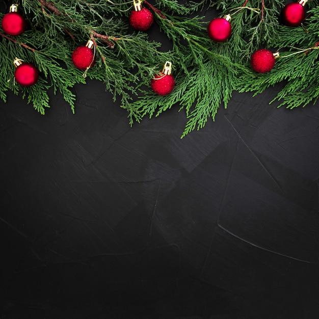 Hojas de pino de navidad decoradas con bolas rojas sobre fondo negro con copyspace Foto gratis