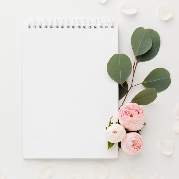 Hojas y rosas con bloc de notas Foto gratis