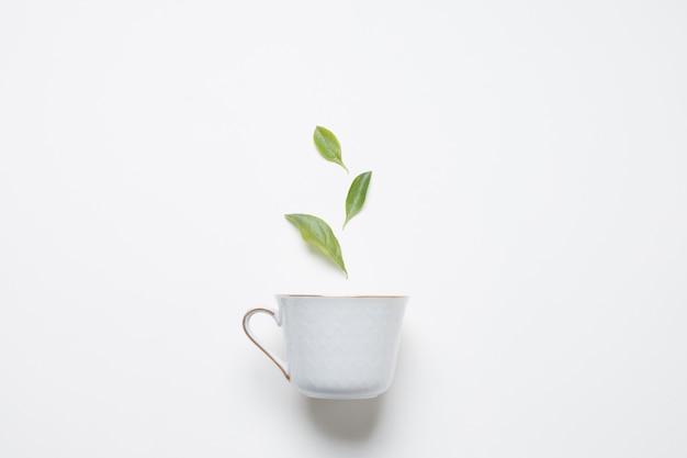 Hojas de té de limón sobre la taza de porcelana sobre fondo blanco Foto Premium