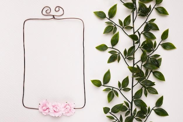 Hojas verdes cerca del marco vacío decorado con rosas rosadas sobre fondo blanco Foto gratis