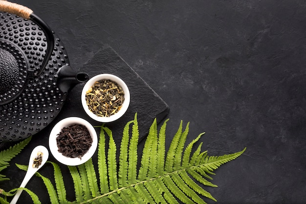Hojas verdes del helecho y hierba seca del té con la tetera negra en fondo negro Foto gratis