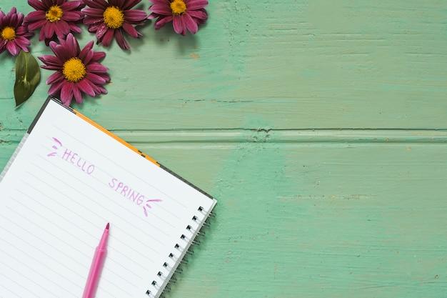 Hola inscripción de primavera en cuaderno con flores. Foto gratis