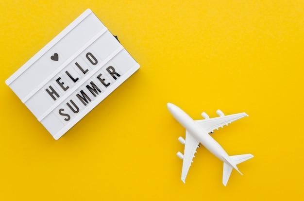 Hola mensaje de verano al lado del avión de juguete Foto gratis