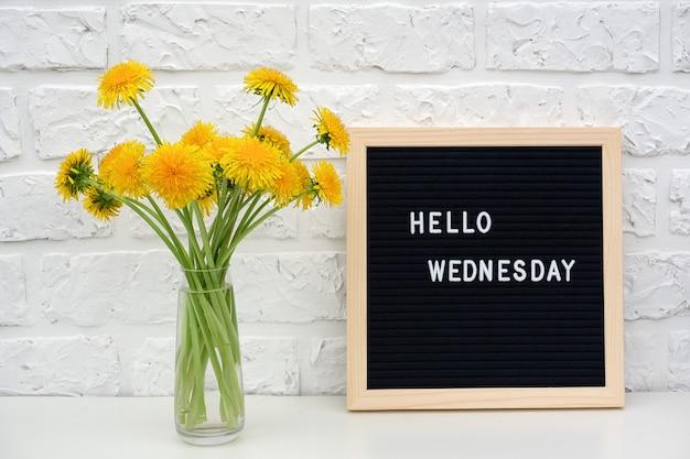Hola palabras del miércoles en el pizarrón negro y el ramo de flores amarillas de diente de león Foto Premium