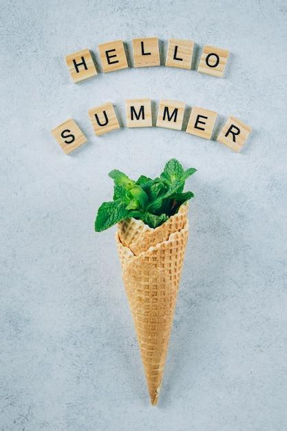 Hola tarjeta de verano. helado creativo con hojas de menta sobre fondo azul Foto Premium