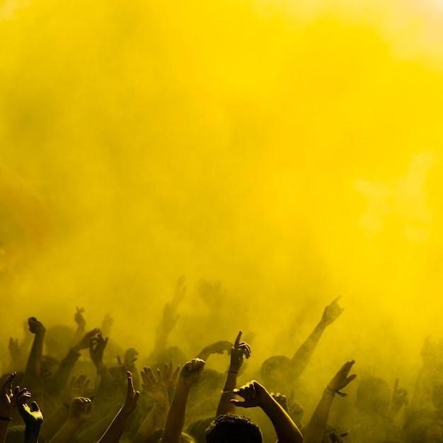 Holi color amarillo sobre las personas bailando. Foto gratis