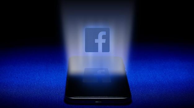 Holograma del logo de facebook. imagen del logotipo de facebook del holograma sobre fondo azul. Foto Premium